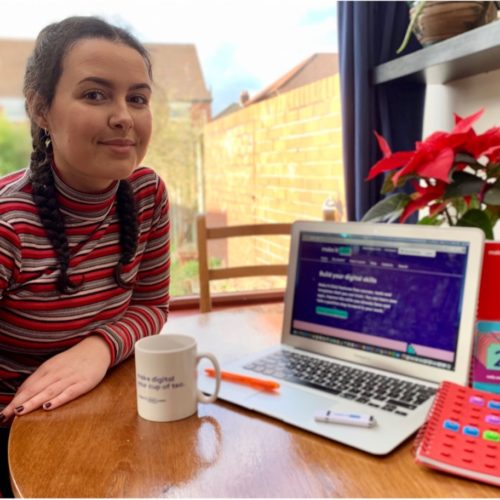 Photo of marketing trainee Maya sitting at table with laptop and Make It Click notebooks