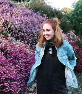 College student Beth Godfrey beside wall of flowers